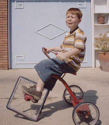 Child riding a tricycle with a square front wheel.